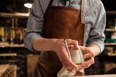 Imagen cosechada de un zapatero que mide un zapato imagenes de archivo