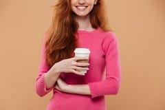 Imagen cosechada de una muchacha sonriente del pelirrojo que sostiene la taza de café Imagenes de archivo