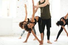 Imagen cosechada de una mujer de ayuda del instructor de la yoga a estirar imagenes de archivo