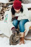 Imagen cosechada de una mujer que frota ligeramente un gato en la nieve Imágenes de archivo libres de regalías