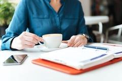 Imagen cosechada de una mujer que se sienta en la tabla del café Imágenes de archivo libres de regalías
