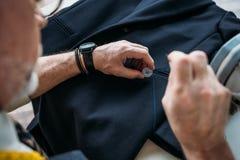 imagen cosechada del botón de costura del sastre a la chaqueta imagen de archivo