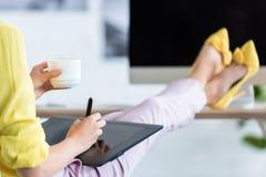 imagen cosechada del café de consumición y de usar del freelancer de sexo femenino la tableta gráfica en la tabla con el ordenado fotos de archivo libres de regalías