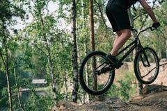 imagen cosechada del ciclista extremo masculino que salta en la bici de montaña imagen de archivo