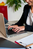 Imagen cosechada del encargado de sexo femenino que trabaja en la computadora portátil Imagen de archivo libre de regalías