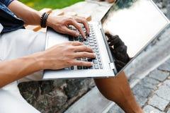 Imagen cosechada del estudiante masculino asiático que usa el ordenador portátil fotografía de archivo