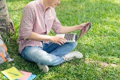 Imagen cosechada del estudiante que se sienta en la hierba verde y el trabajo Imagenes de archivo