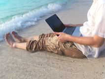 Imagen cosechada del hombre asiático joven relajado con el ordenador portátil que se sienta en la arena de la playa tropical en d Fotografía de archivo