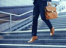Imagen cosechada del hombre de negocios que camina abajo de las escaleras Foto de archivo