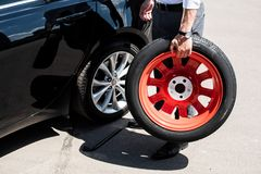 imagen cosechada del hombre de negocios que sostiene el neumático para el reemplazo de la rueda imágenes de archivo libres de regalías