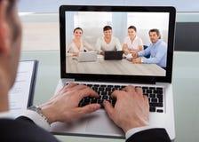 Imagen cosechada del hombre de negocios usando el ordenador portátil en el escritorio Foto de archivo libre de regalías