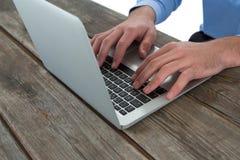 Imagen cosechada del hombre de negocios usando el ordenador portátil en la tabla de madera fotografía de archivo libre de regalías