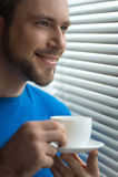 Imagen cosechada del hombre que se coloca con la taza de café Foto de archivo
