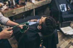 Imagen cosechada del peluquero que aplica perfumes al cliente en el peluquero Imagenes de archivo