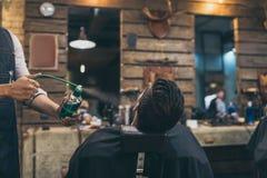 Imagen cosechada del peluquero que aplica perfumes al cliente en el peluquero Imágenes de archivo libres de regalías