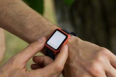 Imagen cosechada del smartwatch moderno en la mu?eca del hombre para comprobar la notificaci?n del smartphone fotos de archivo