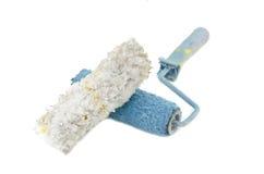 Imagen creativa de la brocha blanca y azul sucia y reutilizada del rodillo con la pluma blanca colocada en frente Foto de archivo libre de regalías
