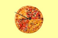 Imagen creativa de la pizza bajo la forma de reloj con las flechas en un fondo brillante hermoso entrega 24 horas de inscripción Imagen de archivo
