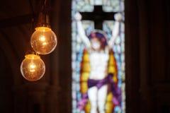 Imagen de bulbos amarillos en el fron de los windos mozaic del colorfull en la iglesia Imágenes de archivo libres de regalías