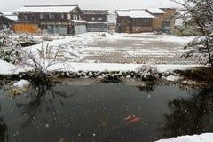 imagen de casas antiguas con arroz y la fosa cuando es la nieve blanca Imagen de archivo
