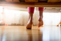 Imagen de debajo la cama en la muchacha que camina en piso de madera en la cama Foto de archivo libre de regalías