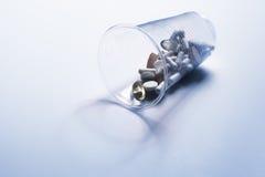 Imagen de diversas píldoras que se derraman fuera de un vidrio plástico Fotos de archivo libres de regalías