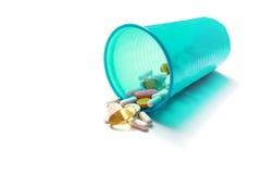 Imagen de diversas píldoras que se derraman fuera de un vidrio plástico Imagen de archivo