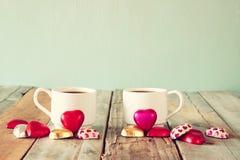 Imagen de dos chocolates de la forma del corazón y tazas rojos de los pares de café en la tabla de madera Concepto de la celebrac Fotos de archivo