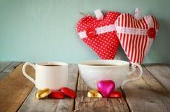 Imagen de dos chocolates de la forma del corazón y tazas rojos de los pares de café en la tabla de madera Concepto de la celebrac Imágenes de archivo libres de regalías