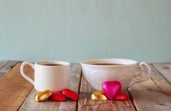 Imagen de dos chocolates de la forma del corazón y tazas rojos de los pares de café en la tabla de madera Concepto de la celebrac Imagen de archivo