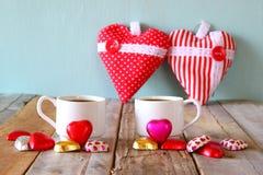Imagen de dos chocolates de la forma del corazón y tazas rojos de los pares de café en la tabla de madera Concepto de la celebrac Fotografía de archivo