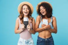 Imagen de dos muchachas felices 20s de las vacaciones con diverso color de SK imagenes de archivo