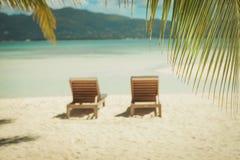 Imagen de dos sunbeds en la playa, debajo de las palmeras Imagen de archivo