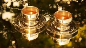 Imagen de espejo de oro de dos tazas de café Foto de archivo