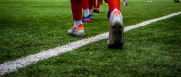 Imagen de falta de definición de los fútboles que caminan en campo verde Fotos de archivo libres de regalías