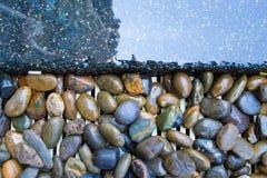 Imagen de fondo con las piedras grandes hermosas y una línea de agua azul de la piscina imagen de archivo