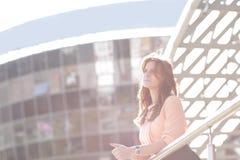 Imagen de fondo de una mujer de negocios de empollamiento que se coloca en el balcón de un edificio de oficinas Imagen de archivo libre de regalías