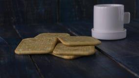 Imagen de fondo de una pequeña taza blanca de café y de galleta salada clásica en una tabla de madera oscura con el copyspace Imagen de archivo
