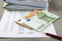 Imagen de ganancias y pérdidas del concepto de una pluma, de una calculadora y de monedas en documentos financieros foto de archivo libre de regalías