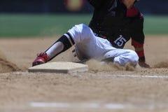 Imagen de la acción del béisbol - los pies primero resbalan dentro de base Imagenes de archivo