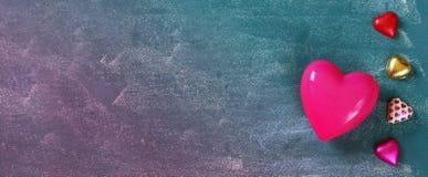 Imagen de la bandera del sitio web de los chocolates coloridos de la forma del corazón en la tabla de madera Concepto de la celeb Imágenes de archivo libres de regalías