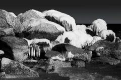 Nevado y rocas heladas en el océano. Blanco y negro Fotos de archivo
