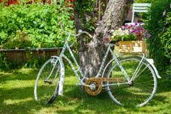 Imagen de la bicicleta vieja del vintage con las flores en la hierba verde Foto de archivo libre de regalías