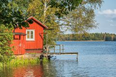 Imagen de la casa escandinava de madera roja del estilo en el lago durante otoño Imagenes de archivo