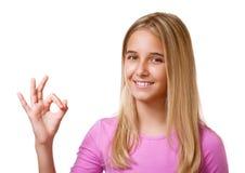 Imagen de la chica joven bonita que muestra la muestra aceptable Aislado Foto de archivo