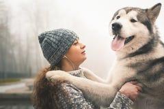 Imagen de la chica joven con su perro, malamute de Alaska, al aire libre Imagen de archivo