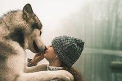 Imagen de la chica joven con su perro, malamute de Alaska, al aire libre Imagen de archivo libre de regalías