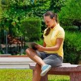 Imagen de la chica joven elegante que usa una PC de la tableta, sentándose en el  Imagenes de archivo