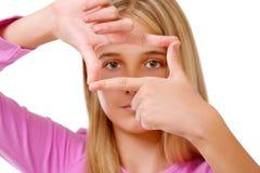 Imagen de la chica joven preciosa que crea un marco con los fingeres isola Imagenes de archivo