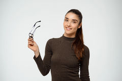 Imagen de la chica joven que sostiene los vidrios en una mano Sobre el fondo blanco Foto de archivo libre de regalías